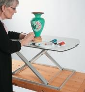 A woman paints a vase on the Height-Adjustable Work Stand