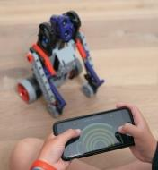 Child operating a robot by remote control through a smartphone