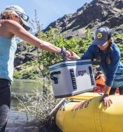 A man and woman load a Yeti Hopper cooler into a raft