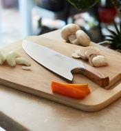 Güde Chef's Knife lying on a cutting board next to sliced vegetables