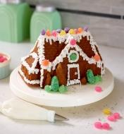 A gingerbread house cake decorated with icing and candy