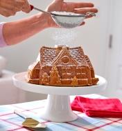 Dusting powdered sugar onto a gingerbread house cake