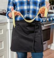 A woman wearing the four-sided apron holds a length of fresh pasta