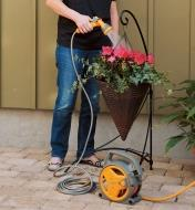 Woman waters a planter on a patio using a Hozelock Pico Reel