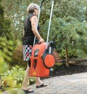 A woman carrying Dual Brush Sweeper with the handle folded