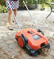 Using the Dual Brush Sweeper to clear debris off a patio
