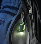 A BugLit rechargeable flashlight hung by the included carabiner on the zipper tab of a backpack