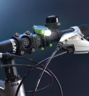 A BugLit rechargeable flashlight's flexible wire arms wrapped around the handlebars of a bicycle