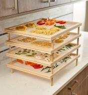 Stack of four mesh trays with pasta and vegetables drying on them