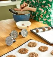 Three cookie stamps sitting next to a tray of cookies that have been stamped, while a woman in the background rolls more cookie dough