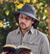 A man wearing an adventure sun hat reads a book outdoors