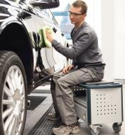 Man sitting on the MMFH 1000 multifunction stool while wiping a car
