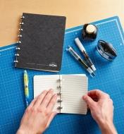 Removing a blank page from the small Atoma notebook, with the large notebook sitting close by