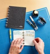 Removing a written-on page from the small Atoma notebook, with the large notebook sitting close by
