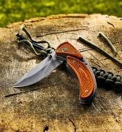 Couteau partiellement plié sur une souche avec des morceaux de corde