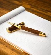 Example of a New Series gold rollerball pen turned from a wood blank, uncapped and lying on a pad of graph paper