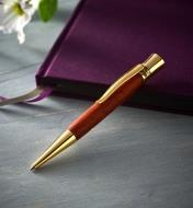 Example of a Glacia gold pen turned from a wood blank, propped on a closed journal