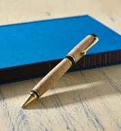 Example of an Olmsted gold pen turned from a wood blank, propped on a notebook