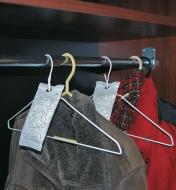 4 oz Deodorizers hanging from clothes hangers in a coat closet