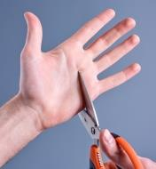 Closing the scissors around a person's hand to demonstrate that they won't cut skin