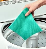 A reusable household paper towel is held ready for dropping into a washing machine