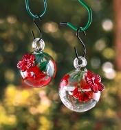 Two hummingbird feeders hanging in a yard