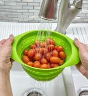 Small collapsible colander used to rinse grape tomatoes under a faucet