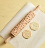 Fleur de Lis patterned rolling pin beside two embossed cookies, comparing before and after baking