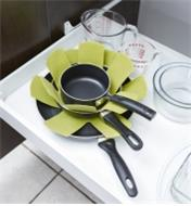 Three pans stacked in a drawer with Pan Protectors between them