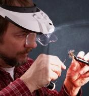 A fly-tyer using an LED headband magnifier while tying a wet fly
