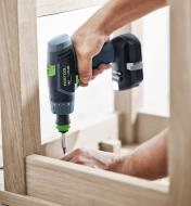 Driving a screw into the underside of a chair with a TXS Cordless Drill