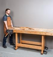 Rolling a workbench into position on a set of four workbench casters