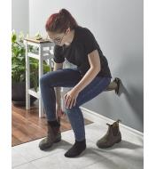 A woman sits on a hall seat while putting on boots