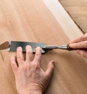 Homme utilisant un ciseau à affleurer Veritas pour araser une large planche