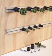 Two tracks including router bits in holders mounted horizontally on a wall