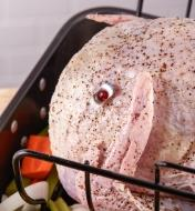 The reusable pop-up turkey timer is inserted in the thickest part of the breast of an uncooked turkey