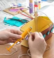 Passage d'une petite corde dans les anneaux du moteur pour bateau miniature afin de le fixer à un bateau jouet maison