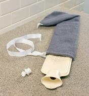 An empty long hot-water bottle sits on a counter, the cover partially removed, ready to fill