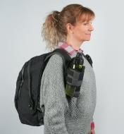 A woman wearing a backpack with a Drink Holster attached