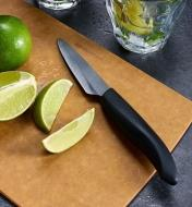 Paring knife on a cutting board with sliced limes