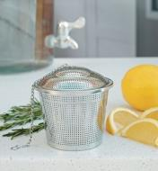 Large Infuser Basket on a counter beside orange slices and rosemary