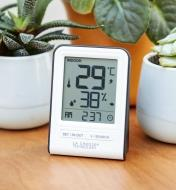 The small secondary display of the Wi-Fi weather station with wind and rain sits on a tabletop