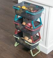 Three medium baskets stacked in a kitchen, holding fruits and vegetables