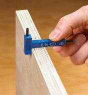 The Kreg material-thickness gauge being used to check the thickness of a plywood panel