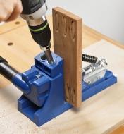 Personne taillant des bouchons pour trous en angle dans une pièce de bois à l'aide d'une perceuse