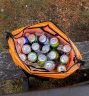 A self-inflating cooler filled with beverage cans and ice