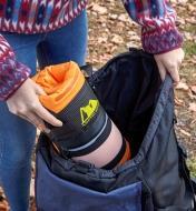 Femme sortant une glacière autogonflante enroulée d'un sac à dos