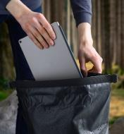 A tablet is placed inside the waterproof dry bag backpack through the roll-top opening