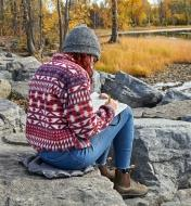 A woman sits on an inflatable seat cushion placed on a rock while writing notes outdoors