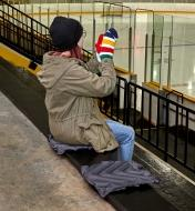 A woman sits on an inflatable seat cushion in the bleachers of a skating rink